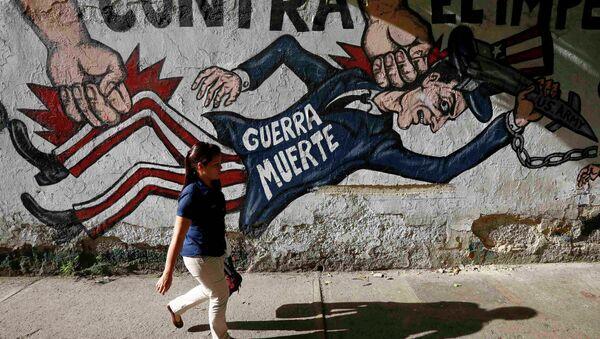 A woman walks past a graffti which reads war dead, in Caracas March 9, 2015. - Sputnik Mundo