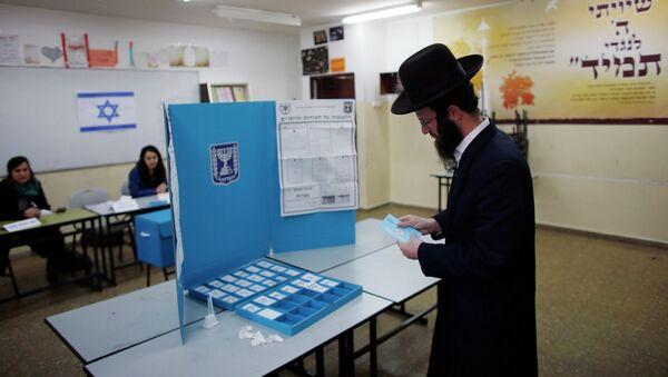 An ultra-Orthodox Jewish man casts his ballot at a polling station in Jerusalem March 17, 2015 - Sputnik Mundo