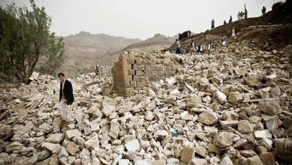 Yemenis stand amid the rubble of houses destroyed by Saudi-led airstrikes in a village near Sanaa - Sputnik Mundo