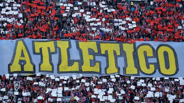 Atletico fans hold up placard in their club colours and the team name  - Sputnik Mundo