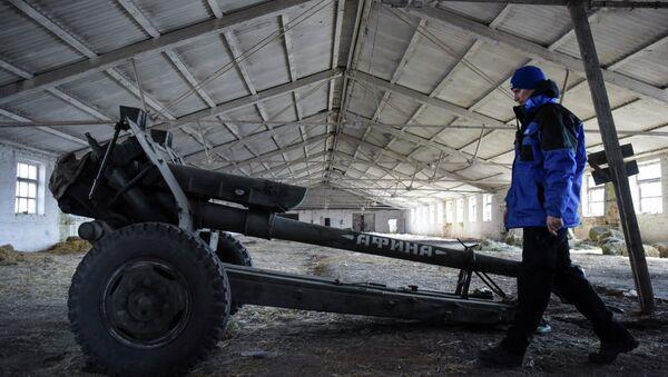 An OSCE monitor inspects a cannon stored by pro-Russian rebels in the village of Novoamvrosiivske, eastern Ukraine, Friday, March 20, 2015. - Sputnik Mundo