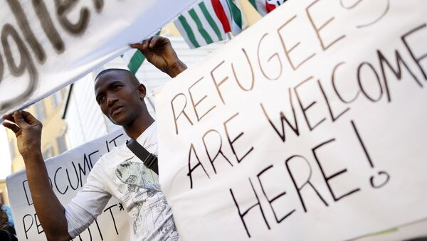 A migrant holds a placard during a protest in front of the Italian Chamber of Deputies in Rome - Sputnik Mundo