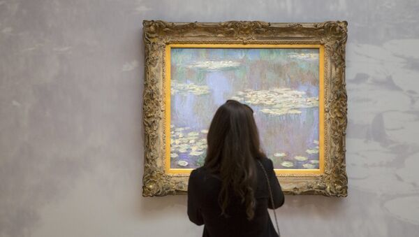 A woman views an example of Claude Monet's Water Lilies, estimated between $35-40 million, ahead of a preview event to Sotheby's upcoming evening's of impressionist, modern and contemporary art in the Manhattan borough of New York City May 1, 2015. - Sputnik Mundo