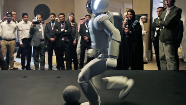 A humanoid robot designed and developed by Honda and named Asimo plays football for the audience at the end of the company's presentation during the last day of the Government Summit in Dubai, United Arab Emirates, Wednesday, Feb. 11, 2015 - Sputnik Mundo