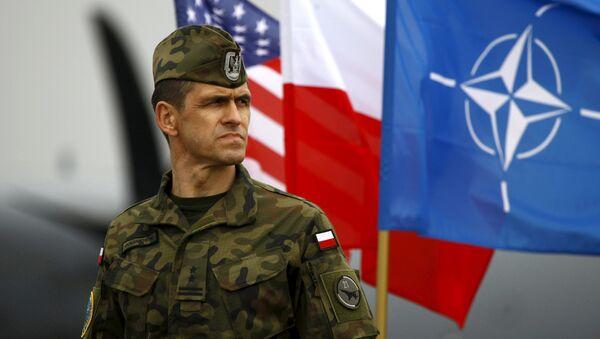 Soldado polaco al lado de las banderas nacionales de los EEUU y Polonia y la bandera de la OTAN - Sputnik Mundo