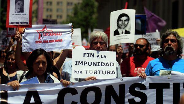Manifestantes con fotos de las víctimas de la dictadura de Augusto Pinochet - Sputnik Mundo