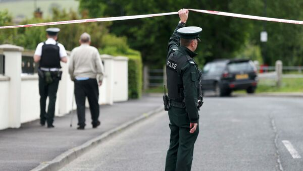 A police officer lifts tape as another escorts an elderly resident on a street closed off after an explosive device was found under a serving police officer's car in Londonderry, Northern Ireland, June 18, 2015. - Sputnik Mundo