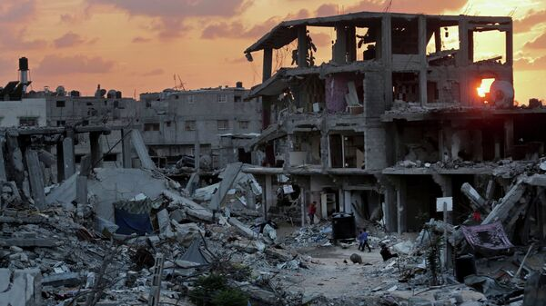 Palestinians walk during the sunset between the rubble of their destroyed building in Shijaiyah neighborhood of Gaza City in the northern Gaza Strip, Sunday, Oct. 12, 2014 - Sputnik Mundo