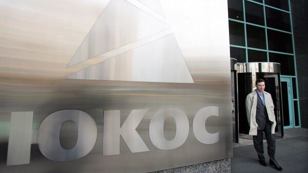 A man passes by a Yukos logo at the headquarters of the oil company in Moscow after the latest auction for the sale of package of assets the stricken giant, 04 April 2007 - Sputnik Mundo