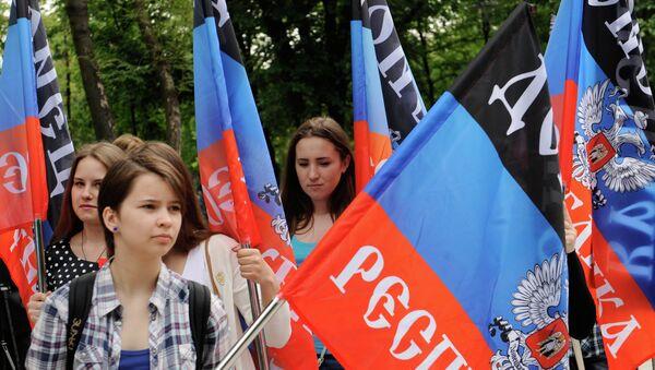 Representantes de la República Popular de Donetsk con las banderas de su república - Sputnik Mundo