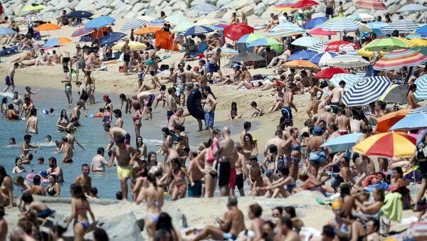 Gente pasa el tiempo en la playa cerca de Barcelona (Archivo) - Sputnik Mundo