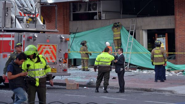 Colombian police officers and firefighters check the site of an explosion in the financial heart of Bogota - Sputnik Mundo