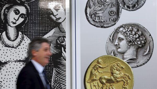 Un hombre camina delante de las monedas en el centro de Atenas, el 13 de julio, 2015 - Sputnik Mundo