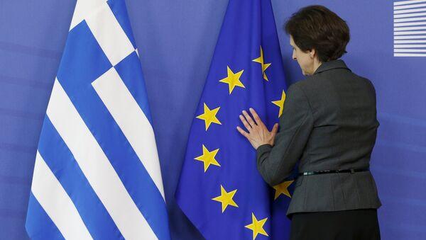 Una mujer ajusta las banderas de UE y Grecia - Sputnik Mundo