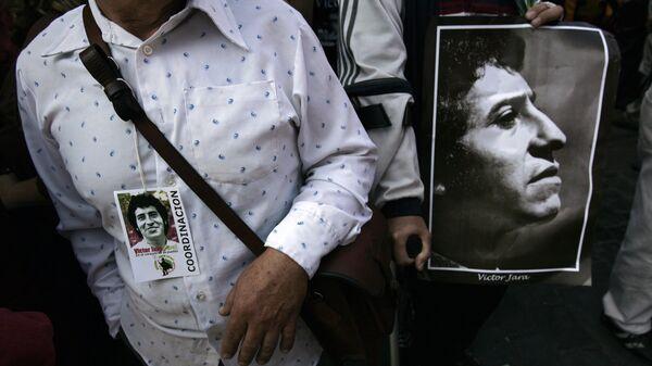 A man holds the portrait of Chilean singer Victor Jara, during his funeral in Santiago on December 5, 2009 - Sputnik Mundo