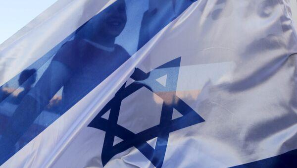 A girl is seen through an Israeli flag during a demonstration - Sputnik Mundo