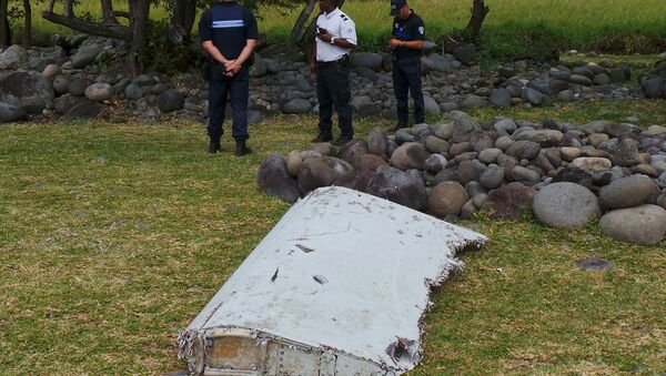 French gendarmes and police stand near a large piece of plane debris which was found on the beach in Saint-Andre, on the French Indian Ocean island of La Reunion, July 29, 2015. - Sputnik Mundo
