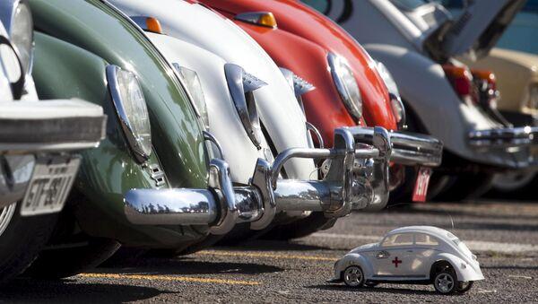 Игрушечная машинка Volkswagen Beetle перед автомобилями-жуками во время праздника в Сан-Бернарду-ду-Кампу - Sputnik Mundo