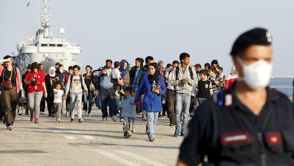 Refugiados sirios acompañados por carabineros italianos después de desembarcar en Augusta, Italia - Sputnik Mundo