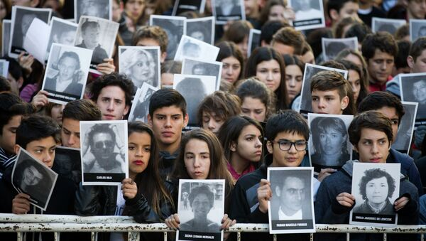People hold pictures of the victims of the 1994 bombing of the AMIA Jewish community center on the 21st anniversary of the terror attack in Buenos Aires, Argentina - Sputnik Mundo
