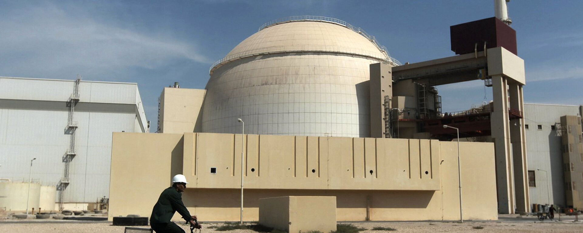 In this Oct. 26, 2010 file photo, a worker rides a bicycle in front of the reactor building of the Bushehr nuclear power plant, just outside the southern city of Bushehr. - Sputnik Mundo, 1920, 17.02.2021