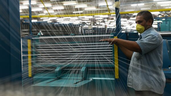 In this photograph taken on July 8, 2014 an Indian employee works at a textile factory in Khatraj village, some 20 kms from Ahmedabad. - Sputnik Mundo