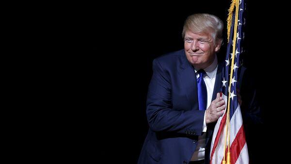 U.S. Republican presidential candidate Donald Trump hugs a U.S. flag - Sputnik Mundo