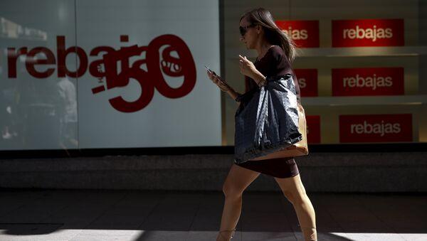 Una mujer pasa cerca una tienda en Madrid, España - Sputnik Mundo