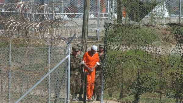 A detainee is escorted to interrogation by U.S. military guards at Camp X-Ray at Guantanamo Bay. - Sputnik Mundo