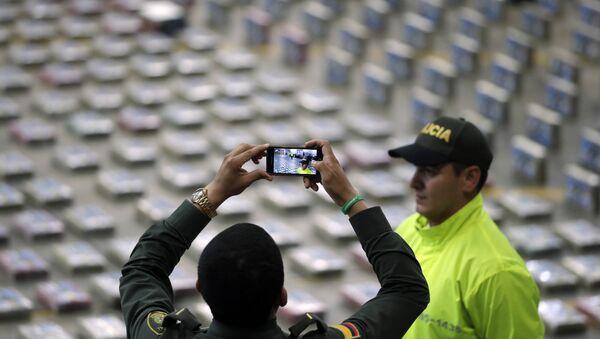 Policía toma fotos de paquetes de cocaína presentados por la Policía para la prensa en Bogota, Colombia (archivo) - Sputnik Mundo