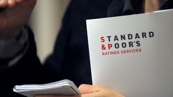 A picture shows Ratings agency Standard & Poor's logo on a document in their Paris office prior a yearly press conference about macro economic outlook and general trends on credit markets, focus on credit condition in France and in Europe by sector in Standard & Poor's offices in Paris on December 8, 2011. - Sputnik Mundo