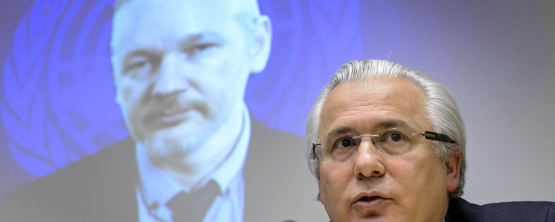 Spanish former judge Baltasar Garzon (R) speaks beneath WikiLeaks founder Julian Assange seen on a screen via web cast from the Ecuadorian Embassy in London during an event on the sideline of the United Nations (UN) Human Rights Council session on March 23, 2015 in Geneva. - Sputnik Mundo, 1920, 23.07.2021