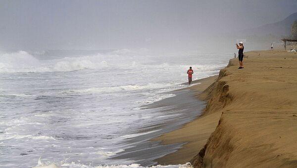 Un hombre toma fotografías de las olas en la playa de Acapulco, México (archivo) - Sputnik Mundo
