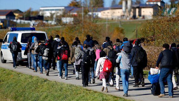 Policía local escolta a un grupo de refugiados despues de cruzar frontera austro-alemana - Sputnik Mundo