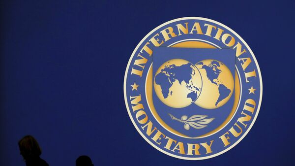 Visitors are silhouetted against the logo of the International Monetary Fund at the main venue for the IMF and World Bank annual meeting in Tokyo in this October 10, 2012 - Sputnik Mundo