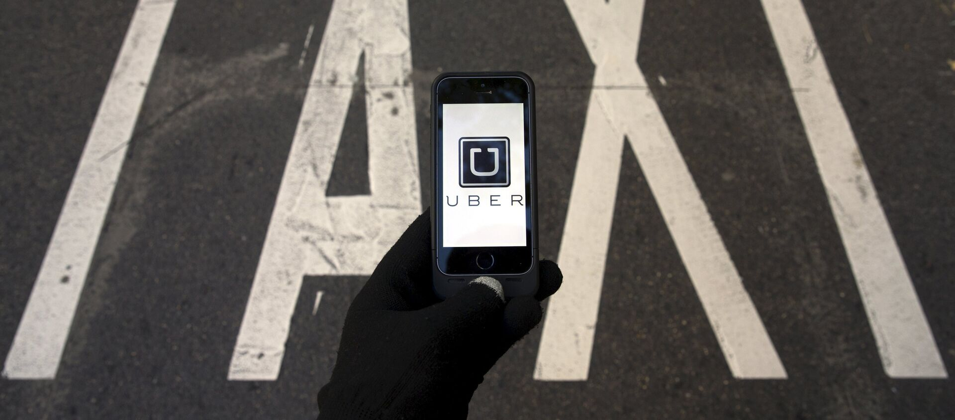 The logo of car-sharing service app Uber on a smartphone over a reserved lane for taxis in a street is seen in this file photo illustration taken in Madrid on December 10, 2014 - Sputnik Mundo, 1920, 02.02.2020