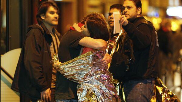 Hombre abraza a una mujer cerca de la sala de Bataclan antes de ser evacuados por autobús - Sputnik Mundo