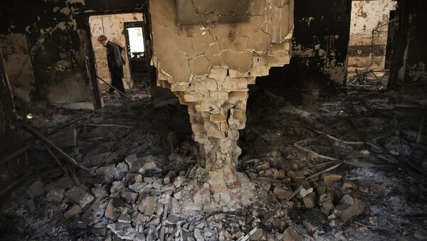 A man wearing a surgical mask walks, 14 October 2015, amongst the debris of the damaged and burnt-out MSF Trauma Centre in Kunduz, northern Afghanistan - Sputnik Mundo