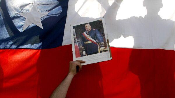 Una foto de Pinochet con bandera chilena del fondo - Sputnik Mundo