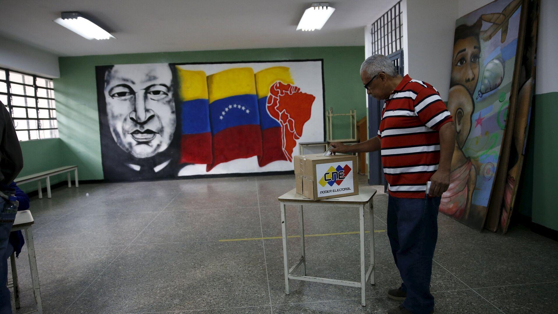 A man deposits his vote in a ballot box near a painting of Venezuela's late President Hugo Chavez during a legislative election, in Caracas - Sputnik Mundo, 1920, 18.03.2021