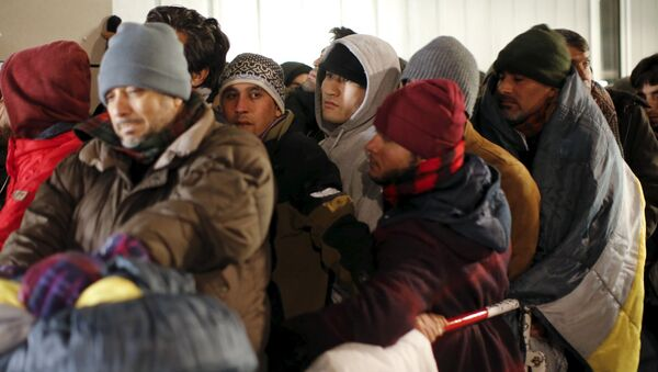 Migrants queue on a street to enter the compound outside the Berlin Office of Health and Social Affairs for their registration process in Berlin - Sputnik Mundo