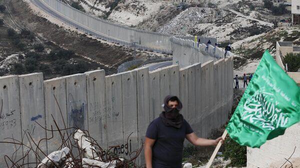 Un palestino con la bandera del grupo islamista Hamás - Sputnik Mundo