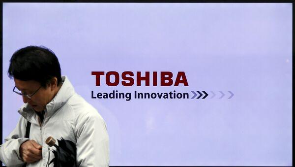 Un hombre pasa por un logo de la empresa japonesa Toshiba - Sputnik Mundo
