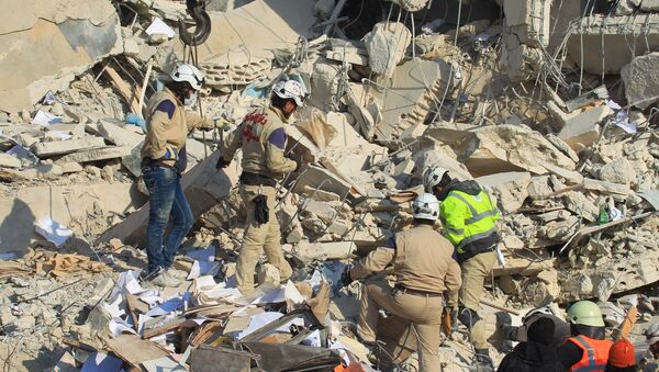 Civil defense members search for survivors at a site hit yesterday by what activists said were airstrikes carried out by the Russian air force in Idlib city, Syria - Sputnik Mundo