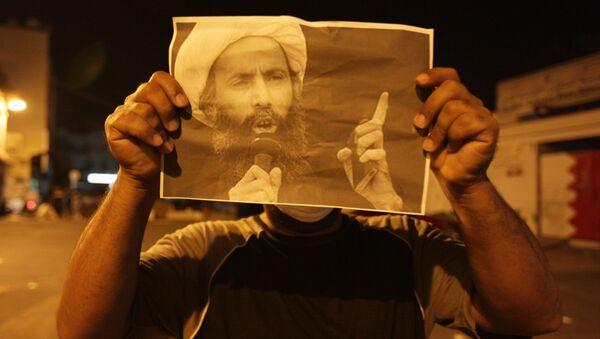 Un manifestante lleva la imagen del clérigo chií Nimr Baqir al Nimr - Sputnik Mundo