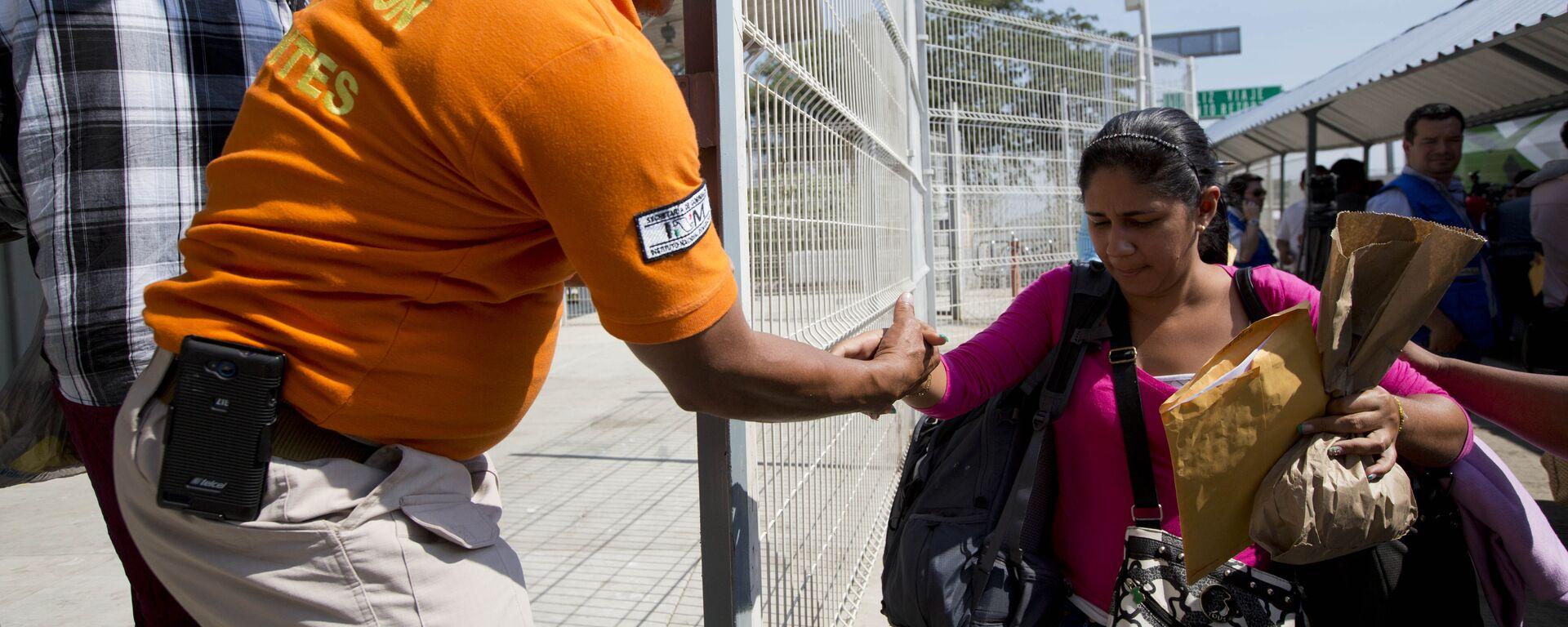Un agent migratorio mexicano ofrece una mano a una migrante cubana cuando llega a Ciudad Hidalgo, México, en la frontera con Guatemala - Sputnik Mundo, 1920, 23.03.2021