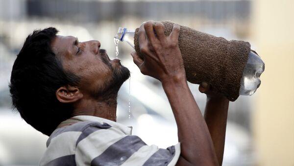 Un hombre bebe agua - Sputnik Mundo