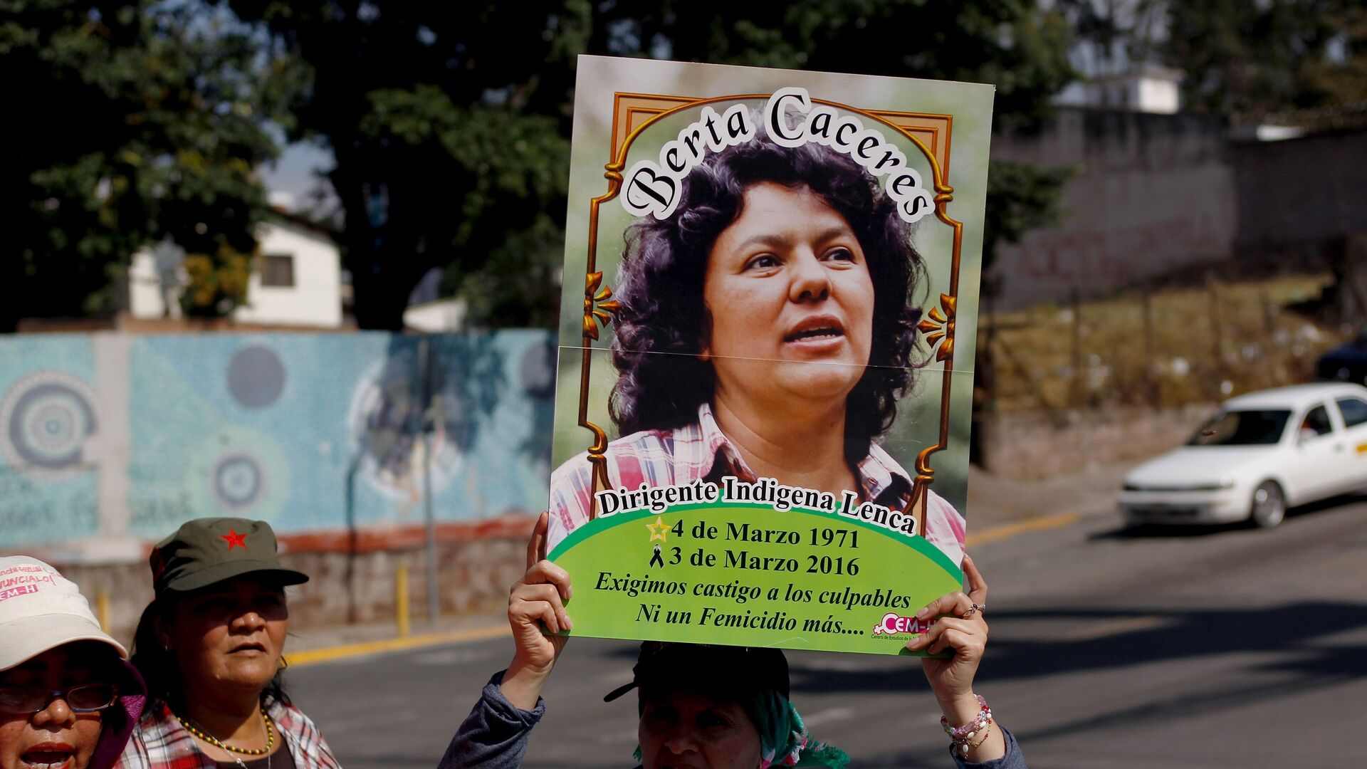 An activist holds up a photo of slain environmental rights activist Berta Caceres during a protest to mark International Women's Day outside the presidential house in Tegucigalpa - Sputnik Mundo, 1920, 20.02.2021
