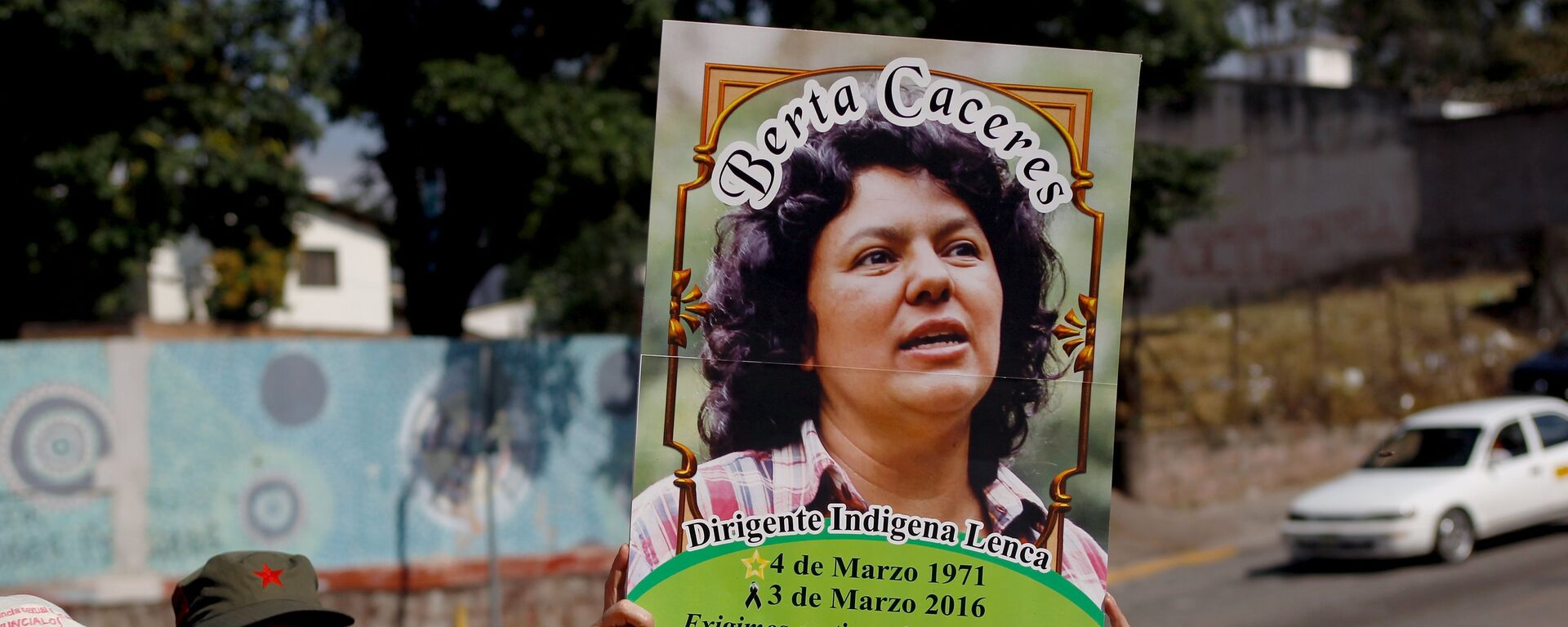 An activist holds up a photo of slain environmental rights activist Berta Caceres during a protest to mark International Women's Day outside the presidential house in Tegucigalpa - Sputnik Mundo, 1920, 25.02.2021