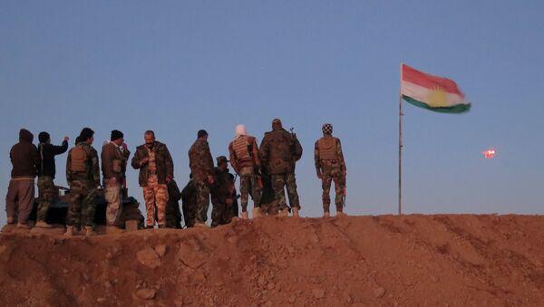 Militantes de Peshmerga cerca de la bandera de Kurdistán iraquí - Sputnik Mundo